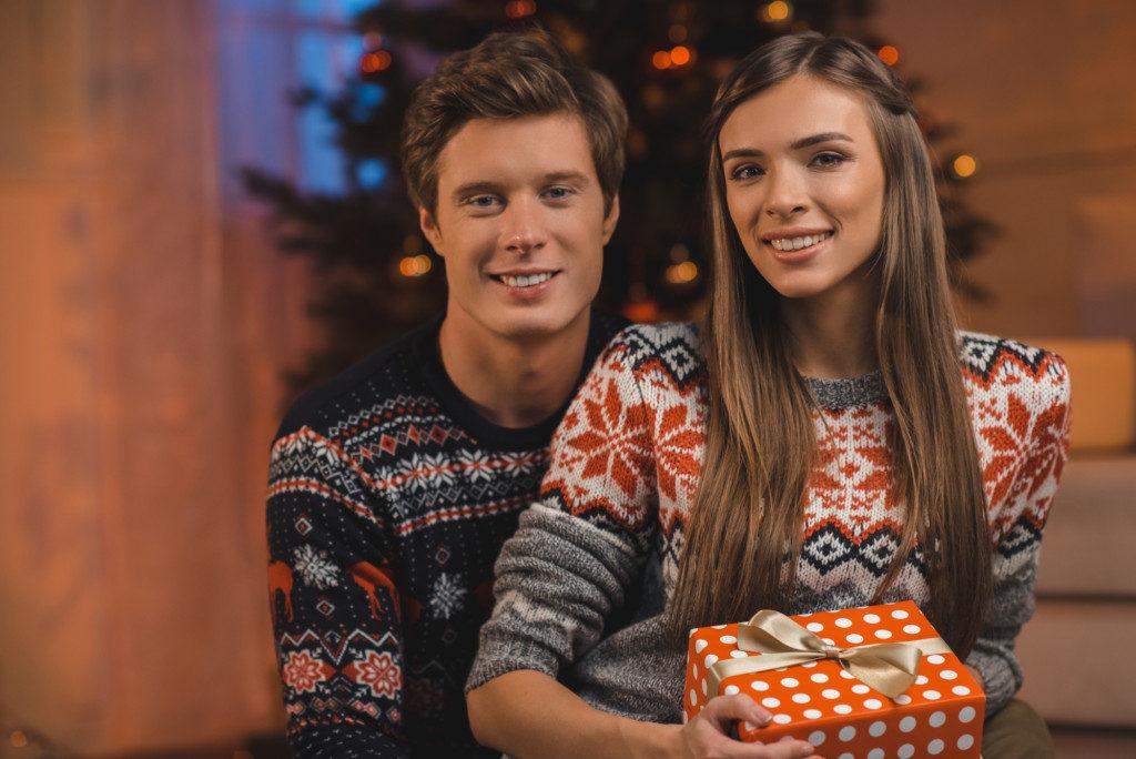 ungt-par-i-stilfulde-julesweatre-foran-deres-juletrae